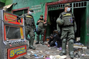 Police officers carry out an operation in an area of Bogotá plagued by drug trafficking and prostitution