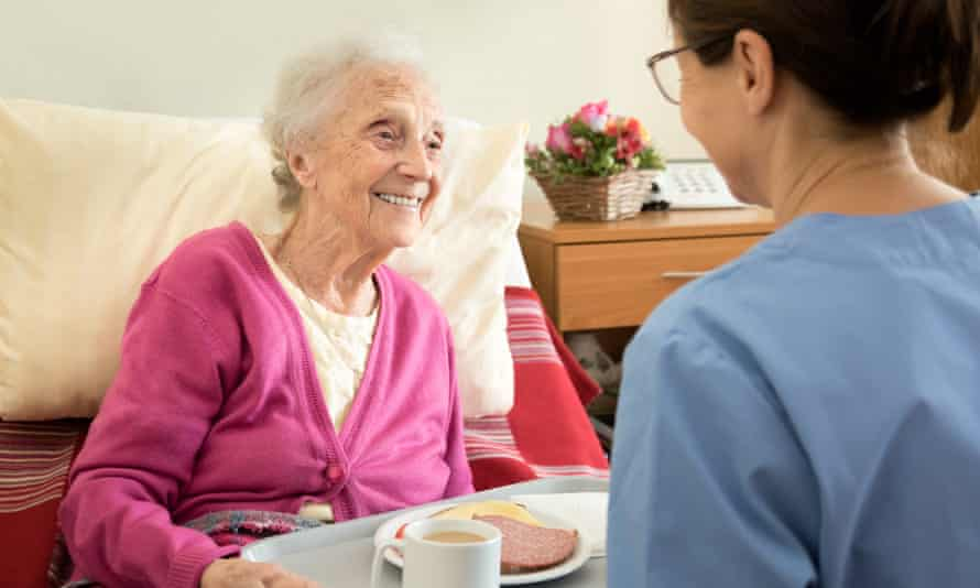 Care worker handing a tray of food to an older woman.