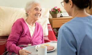 A care worker serves a meal to an elderly woman