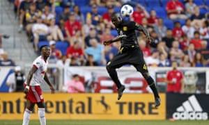 Columbus Crew defender Jonathan Mensah heads the ball in front of New York Red Bulls midfielder Derrick Etienne.