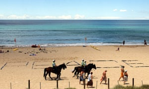 Police patrol an almost empty Cronulla beach a week after the riots
