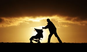 A father is silhoetted as he pushes a pram amid the sunset