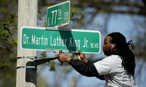 Public works employee Jerry Brooks changes a street sign from The Paseo to Dr. Martin Luther King Jr. Blvd. in Kansas City, Missouri.