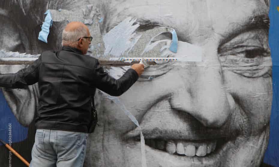 Un activista retira un cartel contra Soros en Budapest, Hungría.