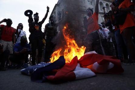 Anti-Trump activists burn a US flag near the White House, 4 July 2020 in Washington DC.