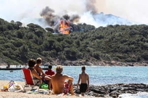 Beachgoers watch a forest fire in La Croix-Valmer, as blazes consume swathes of land in southeastern France.
