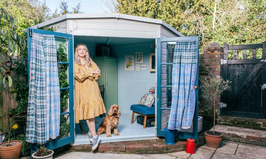 Camilla Perkins standing just inside her blue shed with kantha curtains hanging from the window doors