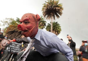 A demonstrator wears a pig mask, a reference to the president, in Bogotá