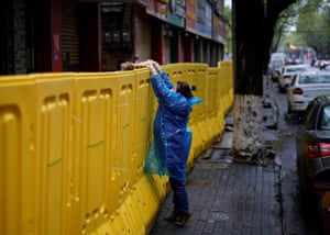Wuhan, ChinaA woman passes eggs over a barricade