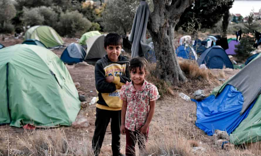 Refugees pose by their shelters on Samos.