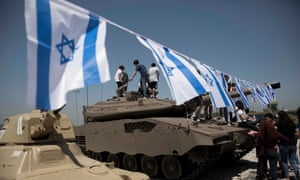 Israeli teenagers climb a tank decorated with flags