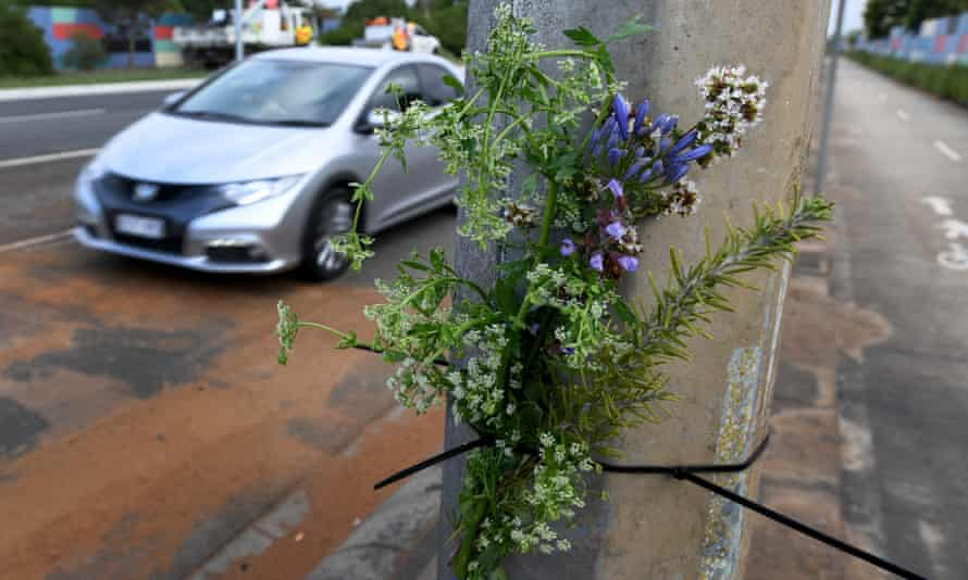 Flowers are viewed at the scene of a fatal car accident.