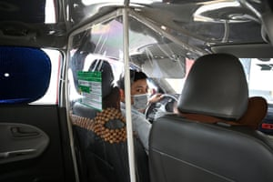 A taxi driver sits behind a plastic screen in Hanoi, Vietnam