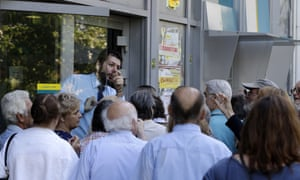 A bank employee gives directions to pensioners in Athens.