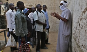 A Libyan smuggler (with covered face) talks to African migrants at a house in Ghat, south-west Libya.