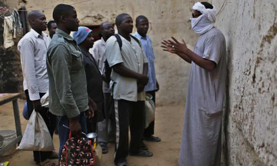 A smuggler (with covered face) talks to a group of men.
