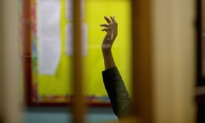 A pupil's raised arm in a classroom