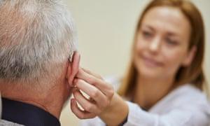 A female doctor applies a hearing aid to an elderly man's ear