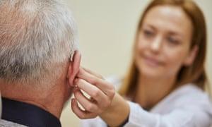 Female doctor applying hearing aid to senior man's ear