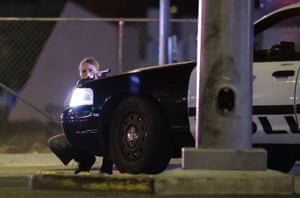 A police officer takes cover behind a police vehicle near the Mandalay Bay resort