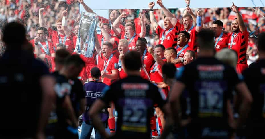 Exeter players look on as Owen Farrell lifts the trophy as he and his Saracens teammates celebrate beating Exeter 37–34 in the Premiership final in June 2019