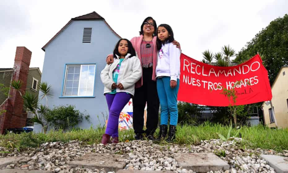 Martha Escudero and her daughters Meztli, left, and Victoria, who were previously homeless, pose in front of their reclaimed home in Los Angeles.