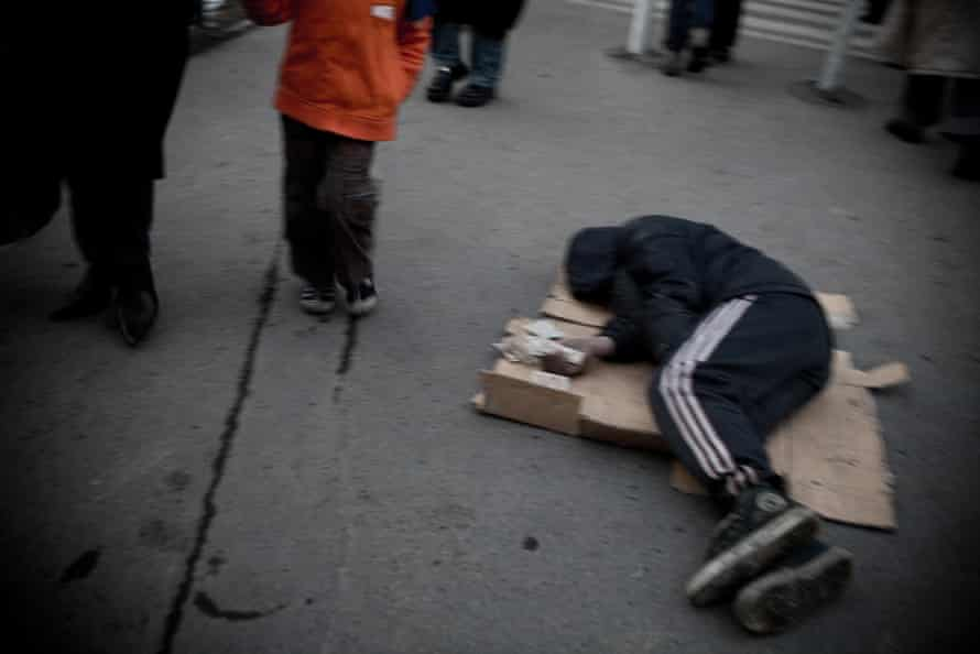A man sleeps near a bus stop in Tehran. Iranians refer to the homeless as 'cardboard sleepers'.