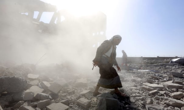 Armed men inspect a Houthi-held detention center after it was hit by alleged Saudi-led airstrikes in Dhamar, Yemen, 1 September 2019.