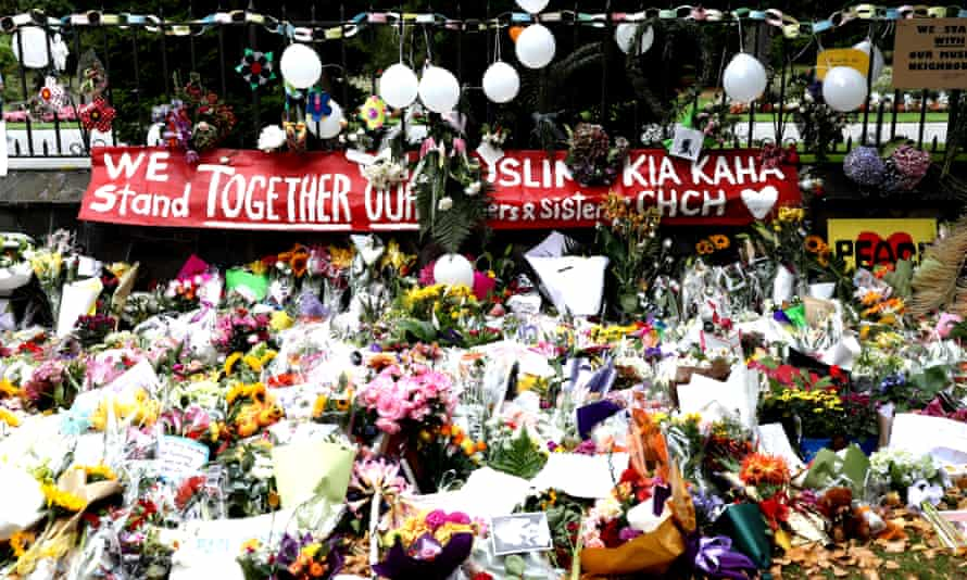 Hundreds of flowers lie on the ground in the front of the fence of the botanic gardens in Christchurch