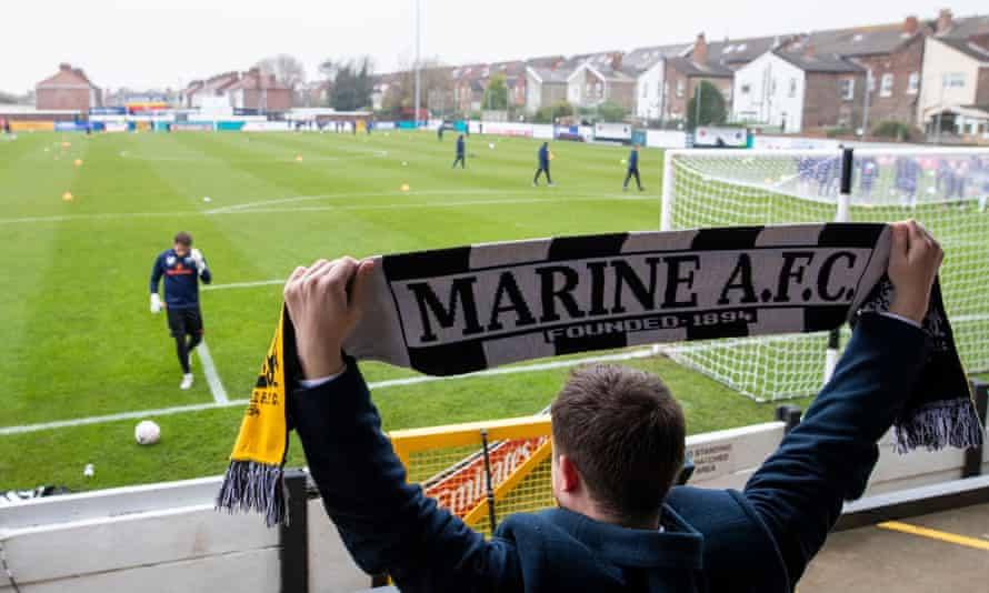 A Marine employee prepares for the second-round tie against Havant & Waterlooville. The only fans watching on Sunday will be residents of the houses overlooking the ground.