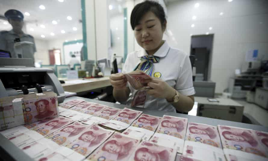 A bank clerk counts Chinese banknotes in Huaibei, Anhui province