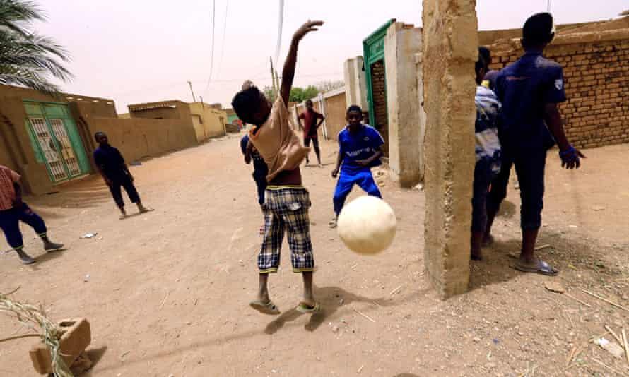 Children play football on the street in Khartoum