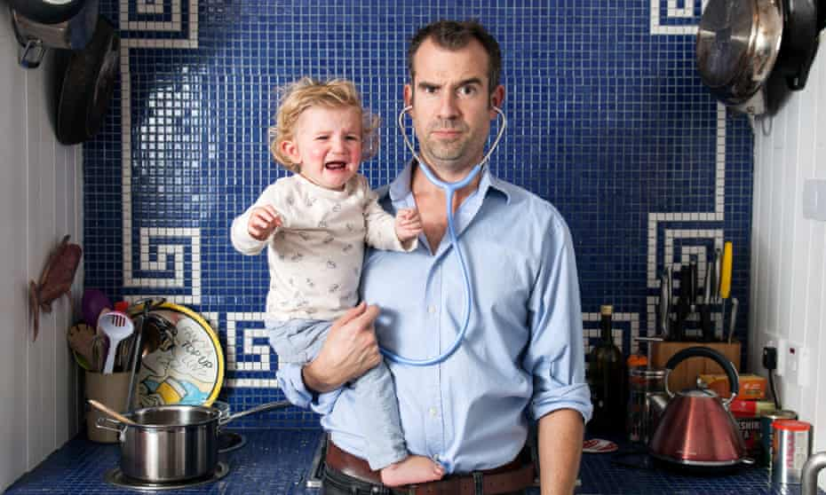 Dr Chris van Tulleken with a stethoscope in his ears holding his crying baby daughter in the kitchen