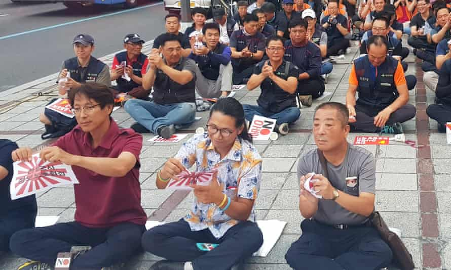 South Korean protesters clap and tear leaflets bearing Japan's rising sun symbol on hearing that the intelligence sharing pact will end.