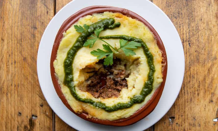 A round terracotta dish of shepherd's pie on a round white plate