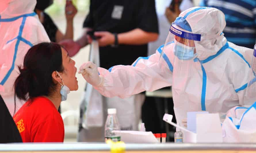 A health worker tests a woman for Covid-19 in China's Hunan province