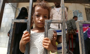 A girl stands behind a fence at a school to which she and her family have been evacuated amid the fighting in Hodeida.