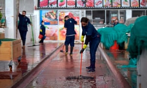 A worker washes the floor at a marketplace before disinfecting it, as a preventive measure against the spread of coronavirus in Bogotá.