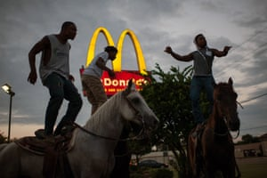Boys and horses in front of a Big mac sign