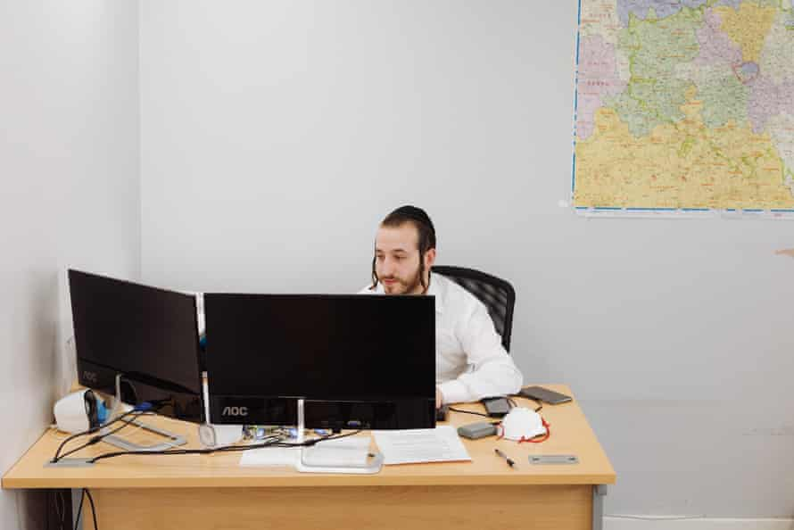 Hershy Tunk, the founder of Lecheiris UK, sits at his desk answering calls
