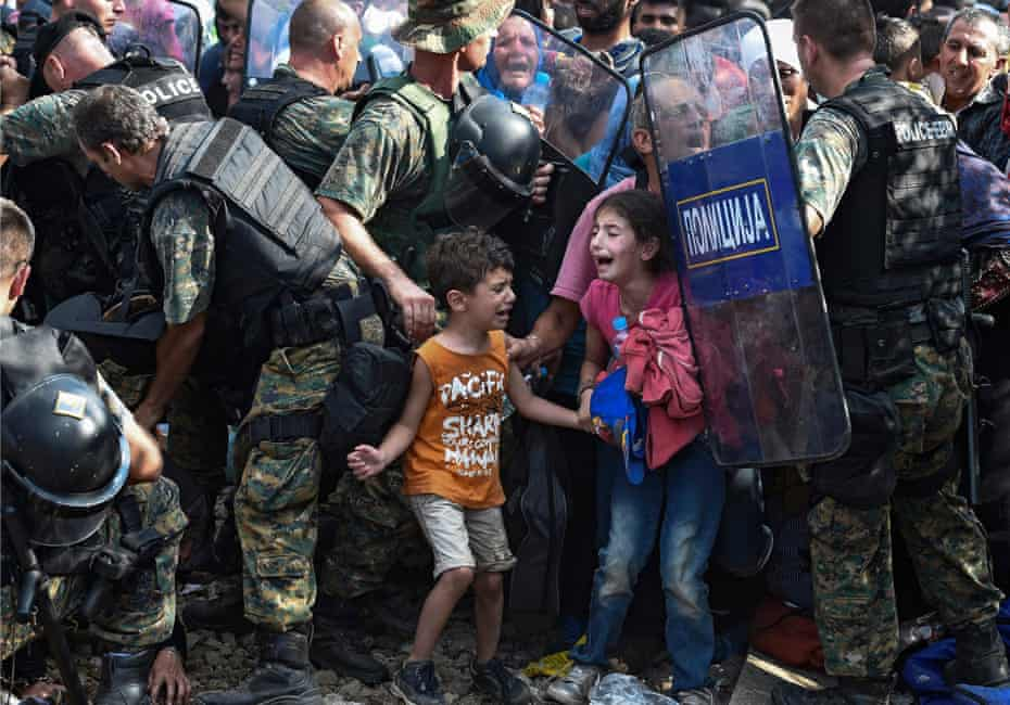 Children cry as migrants waiting on the Greek side of the border break through a cordon of Macedonian special police forces