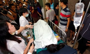 Medics rush an injured person into the emergency room at Police Hospital, where staff were forced to call for Chinese interpreters to help treat foreigners