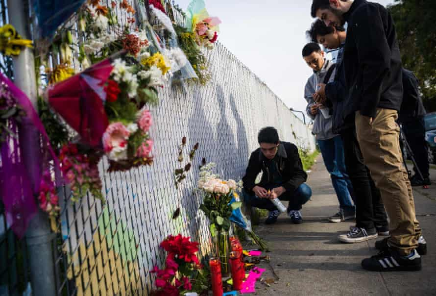 People place flowers and notes at a makeshift memorial in Oakland, near the site of the devastating fire.