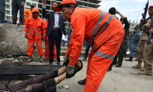 An Afghan municipality worker carries the dead body of a Taliban attacker after clashes with security forces in front of the Parliament, in Kabul, Afghanistan.