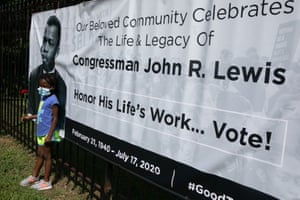 Kelli McLester poses in front of a poster outside of the South View Cemetery where John Lewis is being buried in a private ceremony on Thursday in Atlanta, Georgia.