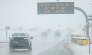 Drivers make their way along snowy roads in Denver.