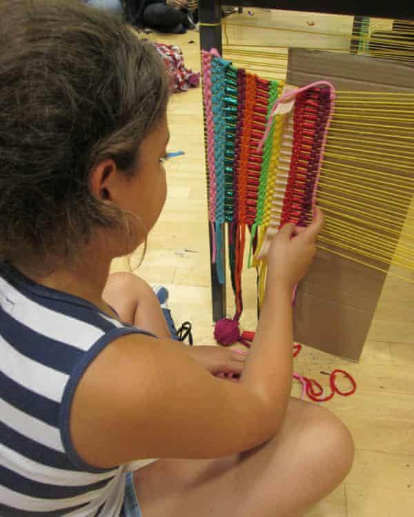 A student learns to weave with yarn made from old clothes.