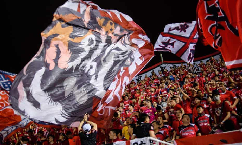 Fans of China's Guangzhou Evergrande wave large flags during the AFC Champions League against Hong Kong's Eastern at Mongkok Stadium