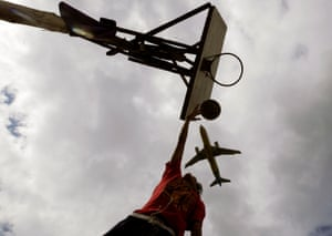A plane flies over a teenager playing basketball in Manila.