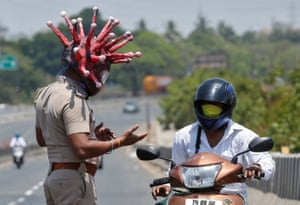 A police officer wearing a helmet depicting coronavirus asks commuter to stay at home